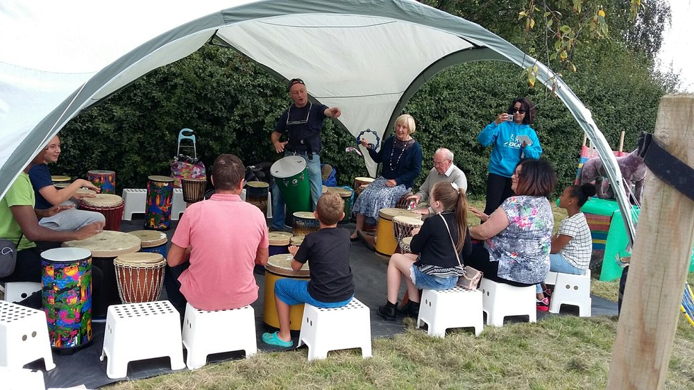 A picture of a group of people drumming together in a tent at Evington Fete.